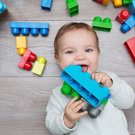 baby holding and surrounded by colorful building blocks with one in its mouth